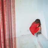 girl in a red dress in the corner of a room