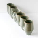 Six hand thrown stoneware vessels, simple forms with decorative marks across one face.